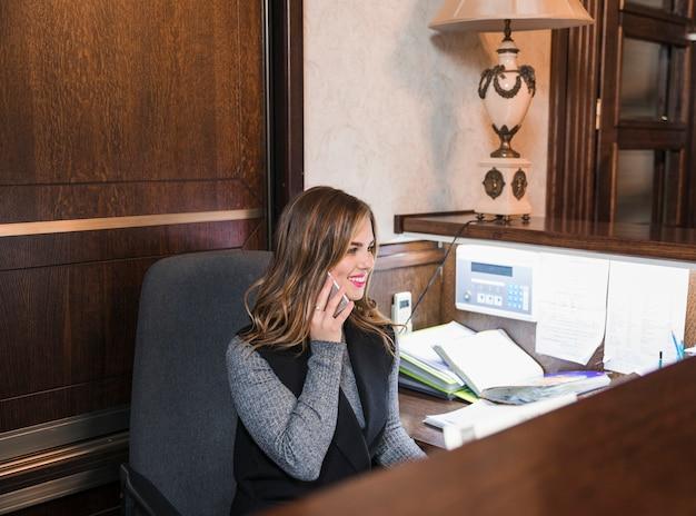 Vrolijke zekere jonge vrouwelijke hotelreceptionnist die op mobiele telefoon spreekt