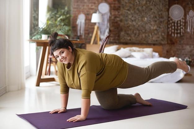 Vrolijke, zelfbepaalde jonge vrouw met rond lichaam en haarknoop die binnenshuis traint op yogamat die de spieren versterkt, beide handen en knie op de vloer houdt, een been opheft en vreugdevol lacht