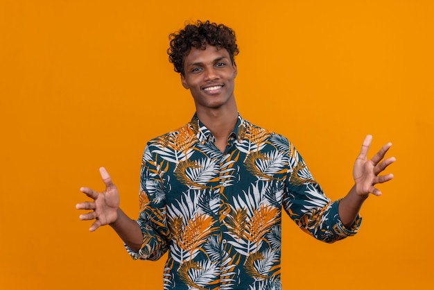 Vrolijke zelfverzekerde knappe donkere man met krullend haar in bladeren bedrukt hemd die zijn handen opent om te knuffelen op een oranje achtergrond