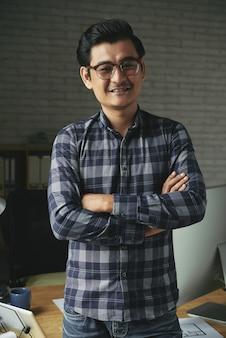 Vrolijke zelfverzekerde man staande armen gevouwen in plaid shirt