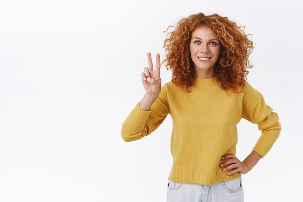 Vrolijke, zelfverzekerde roodharige krullende vrouw in gele trui die vrede toont, teken van goede wil en vastberaden glimlacht, arm op heup houden, streven om te winnen, zelfverzekerd en assertief voelen, witte muur