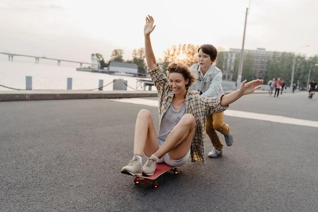 Vrolijke zoon zijn moeder rijden op een skateboard en lachen. alleenstaande moeder tijd doorbrengen met haar zoon buitenshuis