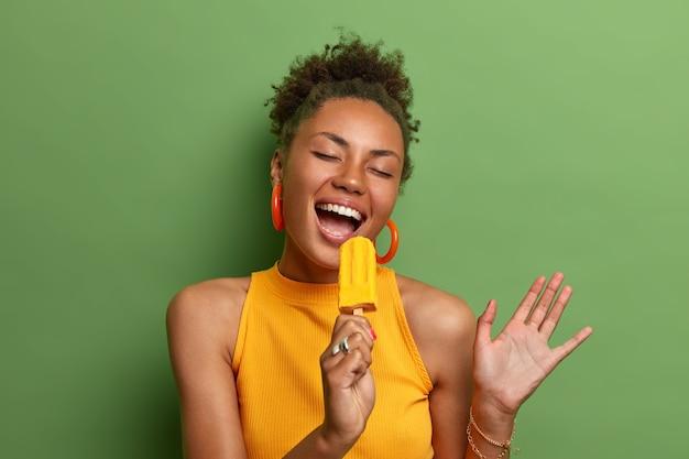 Vrolijke, zorgeloze afro-amerikaanse vrouw zingt in geel ijs zoals in de microfoon, geniet van lekker zomerproduct, is erg blij, geïsoleerd over levendige groene muur, steekt hand op, toont witte tanden