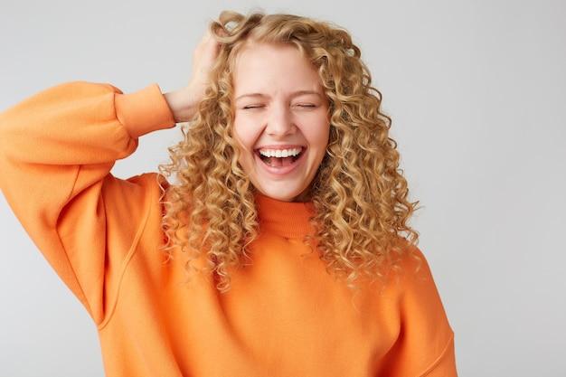 Vrolijke, zorgeloze blije blonde met krullend haar houdt haar hand in de buurt van het hoofd en sluit haar ogen van plezier
