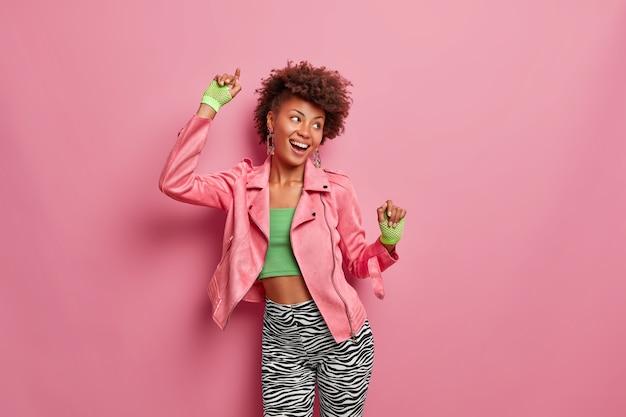 Vrolijke, zorgeloze donkere sportieve jonge vrouw in bijgesneden top en legging, sporthandschoenen, beweegt zorgeloos, verheugt zich over persoonlijke prestaties