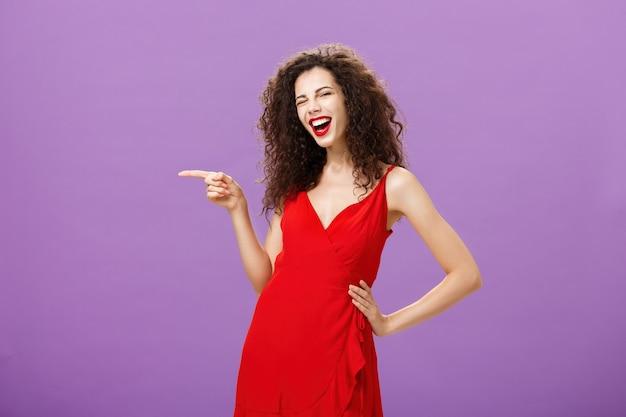 Vrolijke zorgeloze elegante vrouw met krullend kapsel met plezier op geweldig feest in rode luxe dre...