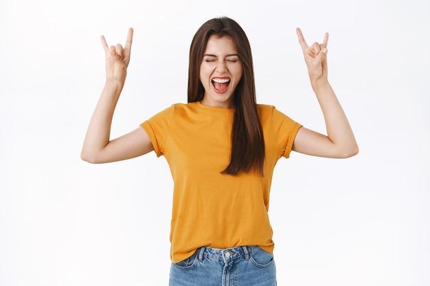 Vrolijke, zorgeloze emotionele gelukkige vrouw die zich wild en vrij voelt, handen opsteken met rock-n-roll, heavy metal teken, glimlachend tong speels tonen, ogen sluiten geniet van geweldig feest, witte achtergrond