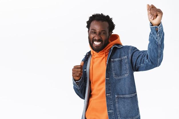 Vrolijke, zorgeloze en ontspannen knappe stijlvolle afro-amerikaanse man die plezier heeft, danst en feesten geniet van een spookachtige halloween-vakantie