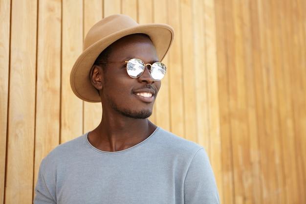 Vrolijke zorgeloze jonge donkere man met spiegelglazen en trendy hoed die gelukkig glimlacht, verheugt zich bij warm zonnig weer, poseren geïsoleerd op houten wal
