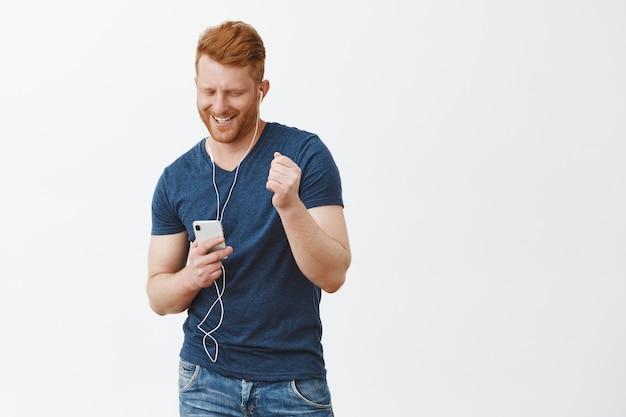Vrolijke, zorgeloze knappe volwassen man met rood haar en spieren, smartphone vasthouden, met brede glimlach naar het scherm staren, muziek in oortelefoons luisteren