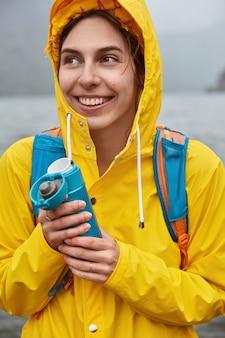 Vrolijke, zorgeloze toerist heeft een vrolijke uitdrukking, kijkt weg en heeft een brede glimlach