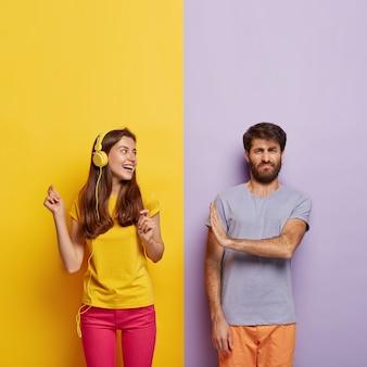 Vrolijke zorgeloze vrouw in casual geel t-shirt, roze broek, luistert naar muziek in moderne koptelefoons