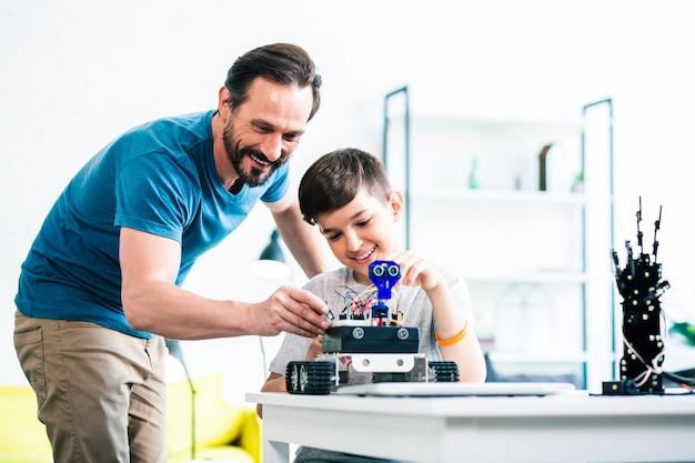 Vrolijke zorgzame vader die zijn zoon helpt terwijl hij samen een robotapparaat bouwt