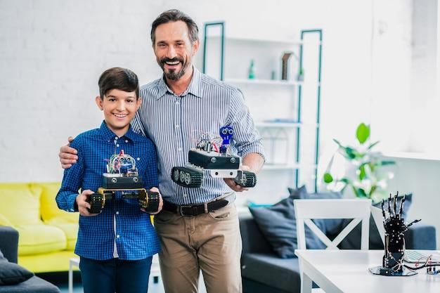 Vrolijke zorgzame vader die zijn zoon omhelst terwijl hij hun robotapparaten bij elkaar houdt
