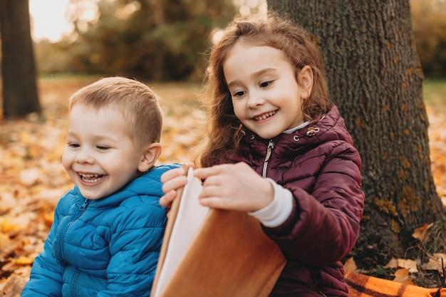 Vrolijke zus zit met haar kleine broertje in het park terwijl ze een boek leest tussen kleurrijke bladeren