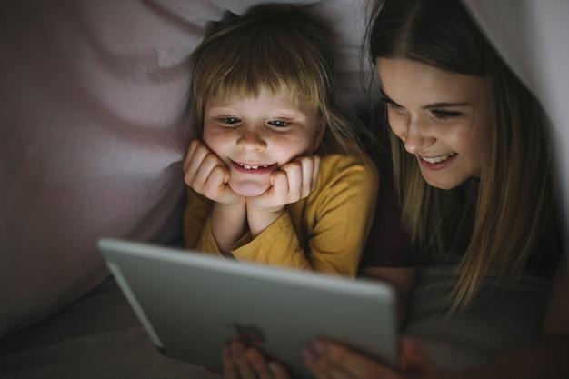 Vrolijke zussen kijken naar film in een deken tent