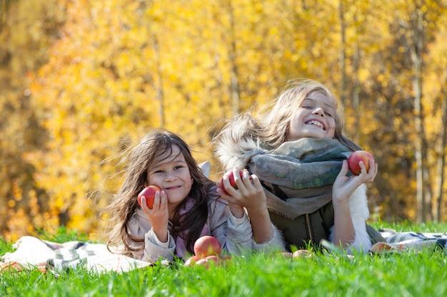Vrolijke zusters die appels op de herfstpicknick houden