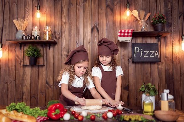 Vrolijke zusters die pizza samen koken