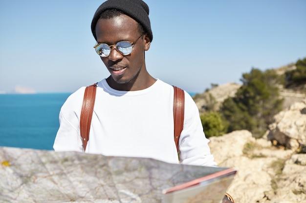 Vrolijke zwarte backpacker in trendy kleding op zoek naar nieuwe interessante plekken om te bezoeken op zijn papieren gids