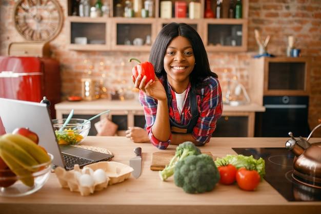 Vrolijke zwarte die gezond ontbijt op de keuken kookt. afrikaanse vrouwelijke persoon die groentesalade thuis voorbereidt