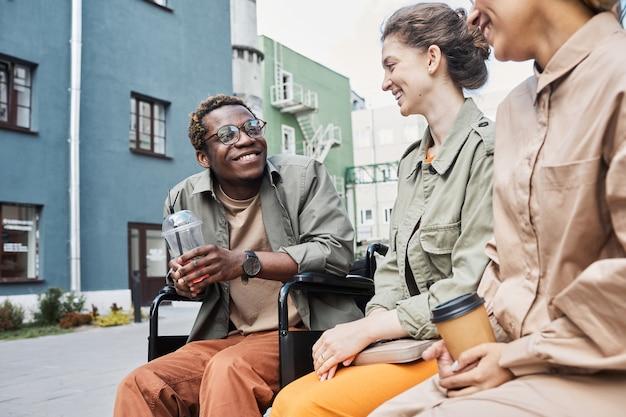 Vrolijke zwarte gehandicapte man die lacht met vrienden