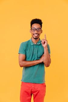 Vrolijke zwarte kerel in grote glazen die positieve emoties uitdrukken. indoor shot van stijlvolle afrikaanse man draagt een rode broek.