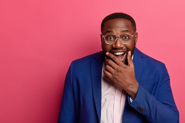 Vrolijke zwarte man baas houdt kin en lacht vrolijk, formeel gekleed, heeft grappige uitdrukking blij gemaakt, lacht om grap