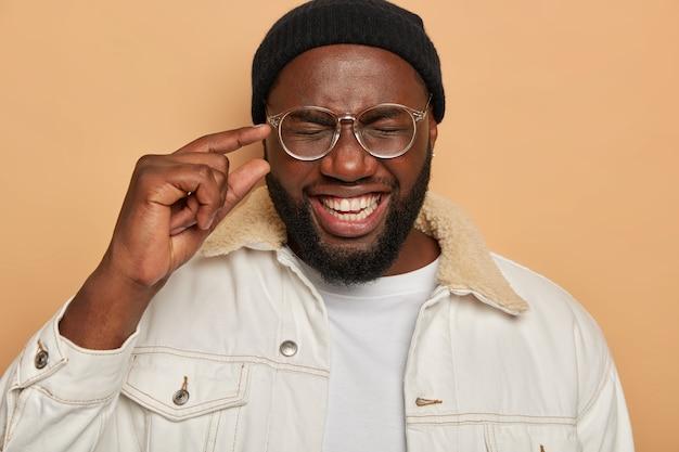 Vrolijke zwarte man maakt weinig handgebaar, glimlacht breed, houdt de ogen gesloten