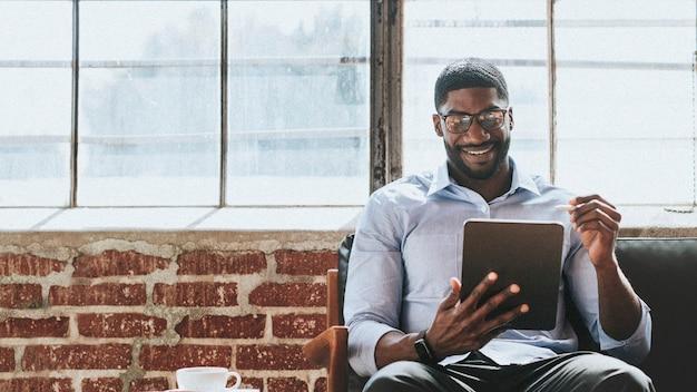 Vrolijke zwarte man met een stylus met een digitale tablet in een woonkamer