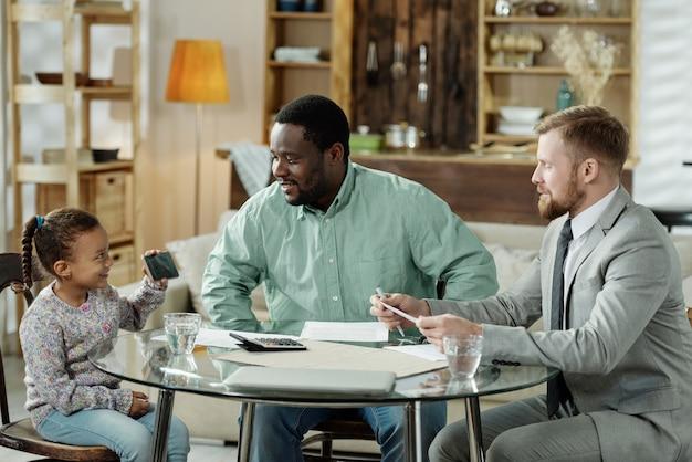 Vrolijke zwarte man met meisje aan tafel met ontmoeting met financieel adviseur aan tafel binnenshuis