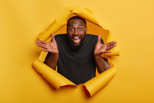 Vrolijke zwarte man spreidt zijn handpalmen, heeft een vrolijke uitdrukking, witte tanden, neemt een beslissing, krijgt een onverwacht aanbod