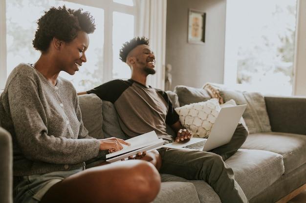 Vrolijke zwarte mensen die een laptop gebruiken
