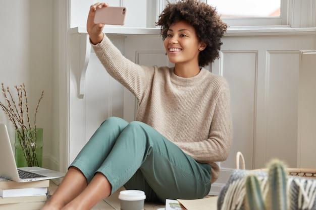 Vrolijke zwarte ontwerper vindt oplossing voor het maken van een briljant project, heeft koffiepauze, maakt videogesprek met mobiele telefoon