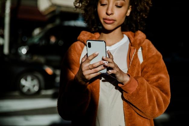 Vrolijke zwarte vrouw die haar telefoon in het centrum gebruikt