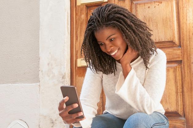 Vrolijke zwarte vrouw die mooie sms van vriend leest