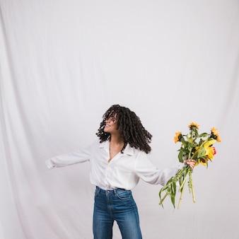 Vrolijke zwarte vrouw houdt van bloemen boeket