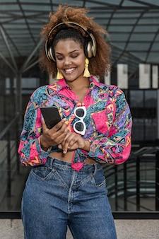 Vrolijke zwarte vrouw in hoofdtelefoon surfen op internet op smartphone