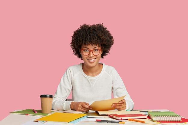 Vrolijke zwarte vrouw maakt creatieve oplossing, houdt papieren document, maakt gebruik van notebook voor het schrijven van notities