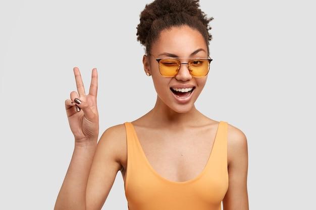 Vrolijke zwarte vrouw met knapperig haar, donkere huid, maakt vredesteken, knippert met de ogen, heeft een positieve uitdrukking, draagt gele tinten, poseert tegen een witte muur. cool african american vrouw gebaren