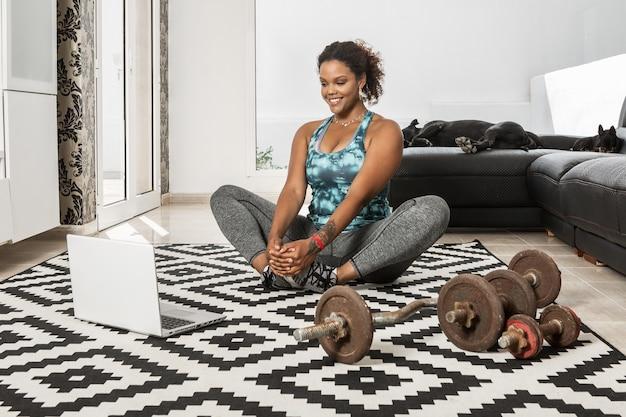 Vrolijke zwarte vrouwelijke atleet in activewear zittend op de vloer en benen strekken tijdens het kijken naar online les tijdens training thuis met honden