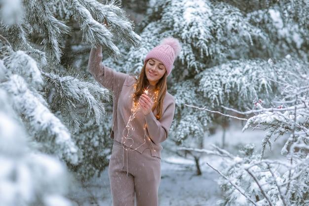 Vrouw 30-35 jaar oud in een warm trainingspak op de achtergrond van een besneeuwd bos met kerstbomen