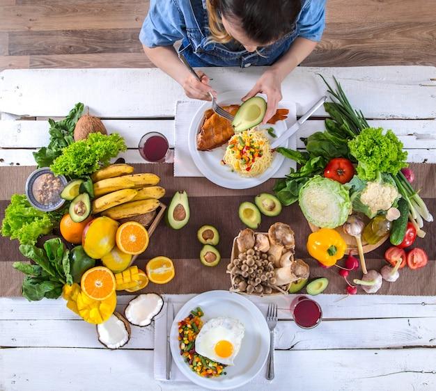 Vrouw aan de eettafel met biologisch voedsel, het uitzicht vanaf de top.