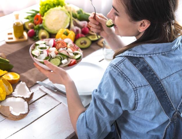 Vrouw aan de eettafel salade eten, bovenaanzicht.
