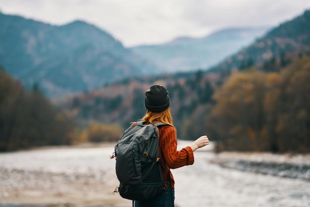 Vrouw aan de oever van de rivier met rugzak reizen wandelen bergen in de verte