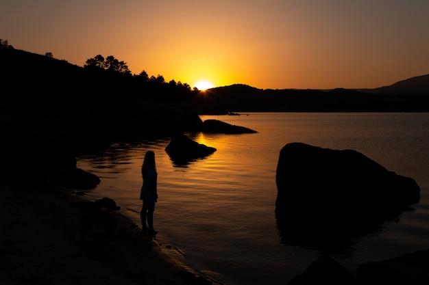 Vrouw aan de oever van een meer bij zonsondergang levensmoeilijkheden overwinnen ruimte kopiëren zelfvertrouwen