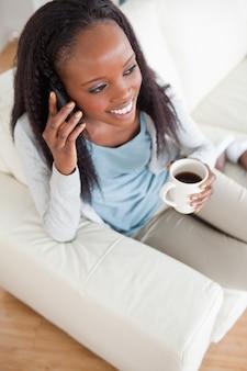 Vrouw aan de telefoon met een kopje koffie