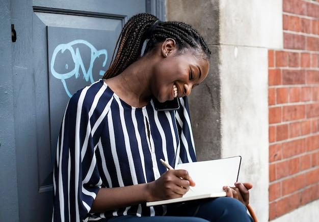 Vrouw aan de telefoon tijdens het maken van aantekeningen