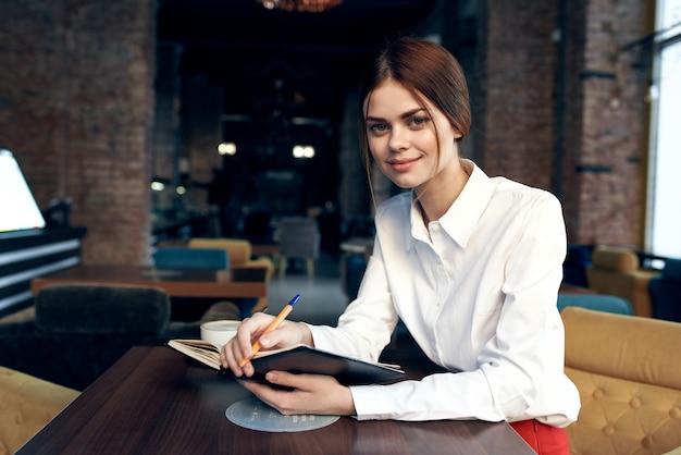 Vrouw aan een tafel in een cafe wit overhemd rode rok kladblok beker op de achtergrond