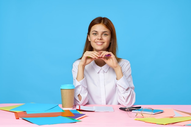 Vrouw aan een veelkleurige tafel glimlacht