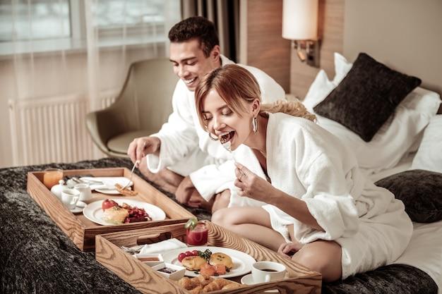 Vrouw aan het eten. blond-haired aantrekkelijke vrouw die stijlvolle oorbellen draagt die lekker ontbijt eten